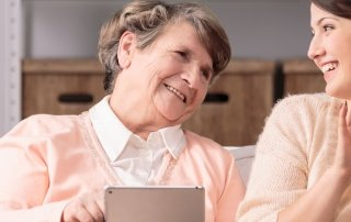 Pflegebedürftigkeit Frau erklärt älterer Dame Technik