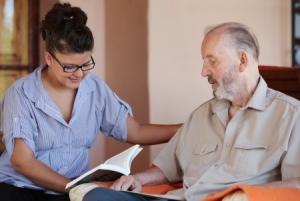 Frau liest pflegebedürftigem Mann aus Buch vor